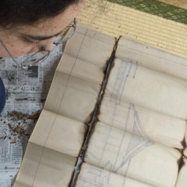 A photo of a person looking at blueprints of a shrine
