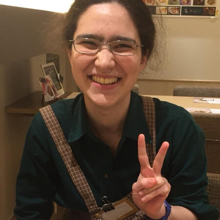 A smiling person in an apron making a victory sign with one hand